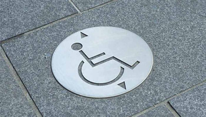 Znak osoby na wózku na chodniku