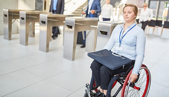 młoda kobieta pracująca w korporacji, poruszająca się na wózku. trzyma torbę.