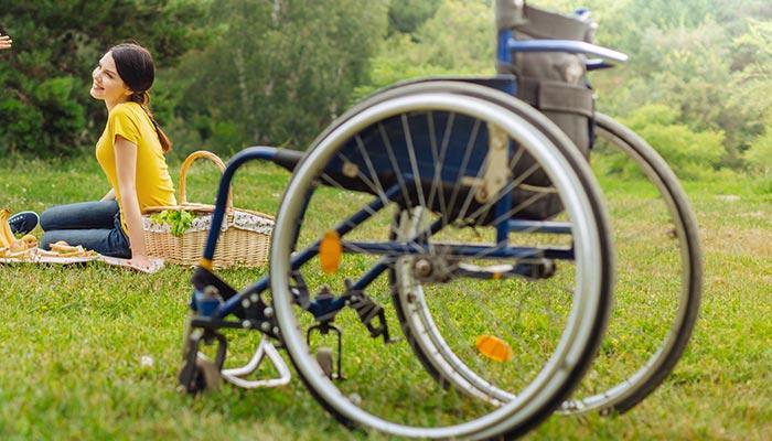 Wózek na zielonej trawie w tle na kocu uśmiechnięta kobieta